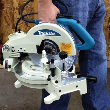 handyman carrying a portable mitre saw